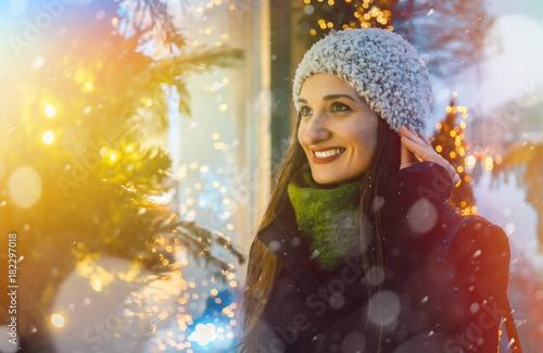 Wall mural Frau schaut in ein Laden Schaufenster an Weihnachten