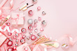 Flat Lay Holiday Background with Christmas ball, gift, ribbon and decorations in pastel pink colour. Flat lay, top view