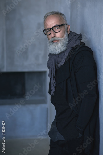 Portrait of calm smart bearded grandfather situating in room Poster