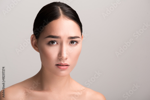 Unhappy. Close-up portrait of young disappointed naked asian woman is standing and looking at camera sadly while feeling depressed. Isolated background with copy space in the right side