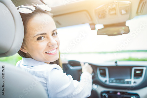 Beautiful young woman sitting in the interior of a new car with a smile.