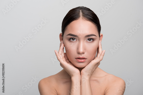 Keuken foto achterwand Spa Natural beauty concept. Portrait of attractive dark-haired young asian woman is touching her skin while posing naked. She is looking at camera confidently. Isolated background