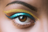 close up of black African woman eye with golden and blue makeup - 182321220