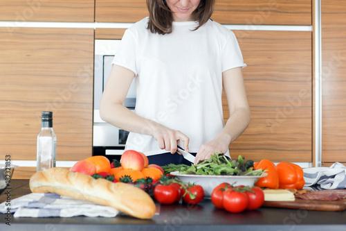 Young woman preparing vagetable salad