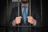 Businessman or politician behind bars in prison cell. - 182323429