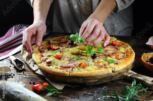 девушка готовит  домашнюю пиццу с базиликом