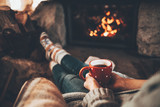 Woman in woollen socks by the fireplace. Unrecognisable relaxes by warm fire with a cup of hot drink and interesting book, warming up her feet. Cozy atmosphere. Winter and Christmas holidays concept.