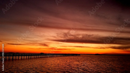 Fotobehang Bruin Dramatic sunset cloudscape with a wooden fishing pier jetty