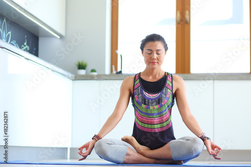 Plexiglas Fitness Young woman doing yoga at home in the lotus position. Yoga. Woman. Lifestyle
