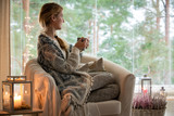 Young beautiful woman sitting home in the chair by the window with cup of hot coffee wearing knitted warm sweater. Cozy room decorated with lanterns and candles.  - 182363257