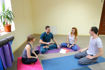 Four young people sit on floor on yoga mats and communicate.
