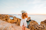 Woman enjoying great view on the rocky coastline during the sunrise in Lagos on the south of Portugal - 182366656