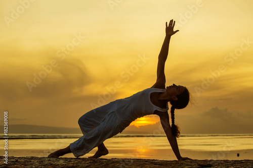 Aluminium School de yoga Woman practices yoga at the seashore at sunset on Bali in indonesia