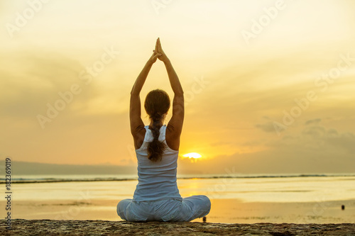 Sticker Woman practices yoga at the seashore at sunset on Bali in indonesia