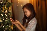 cute girl dresses Christmas tree in Christmas - 182369827