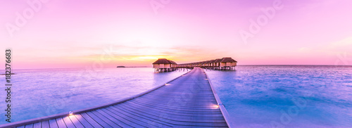 Foto op Plexiglas Purper Sunset on Maldives island, water villas resort. Beautiful sky and clouds. Beautiful beach background for summer travel with sun, beach wooden jetty. Summer mood sun beach background concept.