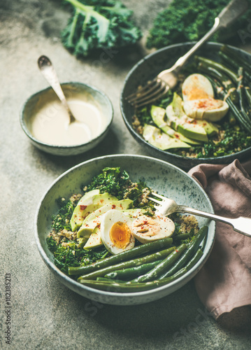 Healthy vegetarian breakfast bowls. Quinoa, kale, green beans, avocado, egg and creamy tahini dressing bowls over grey concrete background, selective focus. Energy boosting, clean eating food concept