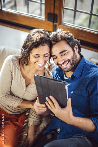 Young Couple Sitting On Sofa Using Digital Tablet Poster