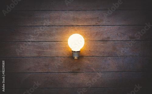 Light on bulb on wooden background.
