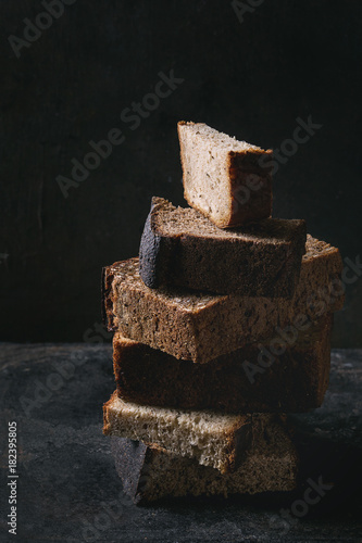 Variety loaves of sliced homemade rye bread whole grain and seeds in stack over old dark background. Close up. Healthy eating
