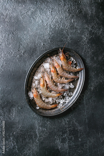Raw whole fresh uncooked prawns shrimps on ice on vintage metal tray over black texture background. Top view with copy space
