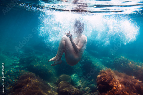 Naked woman with bubbles is underwater swimming in ocean