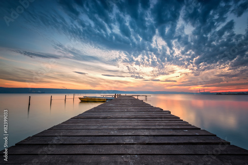 Fotobehang Pier Lake sunset / Magnificent long exposure lake sunset with boats and a wooden pier