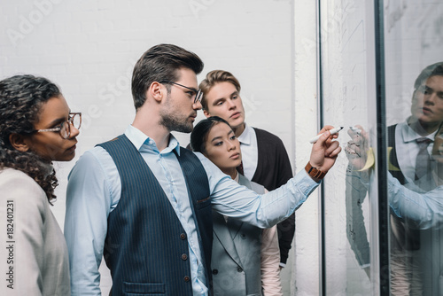 Wall mural multicultural businesspeople writing on glass board and working in office