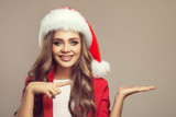 Portrait of cute smiling woman in santa hat. Holding template sample in her hand. Christmas.