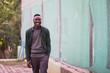 Portrait of stylish african american young man on sportswear,green shirt walking. Black men model street fashion.