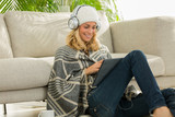 beautiful woman listening music at home with headset winter season - 182406840