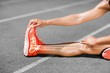 Low section of female athlete stretching on sports track