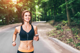 Young fitness girl running and listening music in the park - 182414222