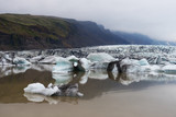 Icebergs in Fjallsarlon glacial lagoon. Picturesque landscape with misty mountains and large glacier. Vatnajokull National Park, southeast Iceland, Europe - 182421009