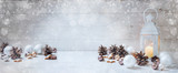 wide christmas background with a candle light lantern, baubles, cinnamon stars and cones on rustic white wood, panorama format for website banner, copy space - 182421401
