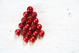 red Christmas balls in the shape of a fir tree on white painted rustic wood, christmas background or greeting card, flat top view from above, copy space - 182421842