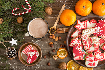 Overhead of Christmas New Year holiday background with gingerbread cookies, fir tree branch, mandarins, cocoa drink over on old wooden table.