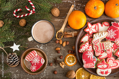 Fototapeta Overhead of Christmas New Year holiday background with gingerbread cookies, fir tree branch, mandarins, cocoa drink over on old wooden table.