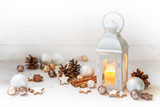 Christmas lantern with burning candle light and decoration like baubles, pine cones and cinnamon star cookies on rustic white wood with copy space - 182422411