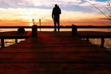 Silhouette of man standing on a wooden dock at sunset. - 182423831