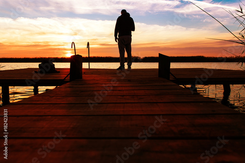 Fotobehang Bruin Silhouette of man standing on a wooden dock at sunset.