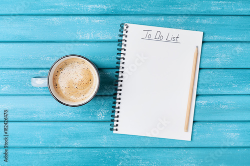 Cup of coffee and notepad with to do list on turquoise wooden table top view. Planning work concept.