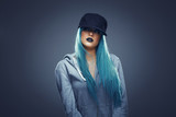 Young woman with cyan color hair in hoodie and cap - 182432680