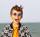 cute little boy at seacoast in fashion clothers and blue glasses - 182439660