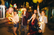 Group of happy friends going on the party, having fun at the street and drinking champagne. New year party. Birthday party