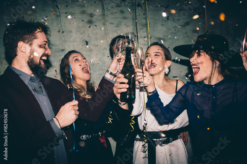 Foto Murales Group of happy friends drinking champagne and celebrating New Year. New year party. Birthday party