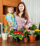 Brunette  with a baby transplanting potted flowers - 182452215