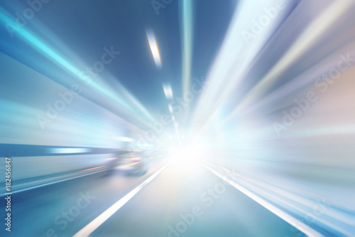 Fototapeta Abstract blurred high speed car driving in the highway tunnel. Motion blur visualizes the speed and dynamics. Personal perspective used.