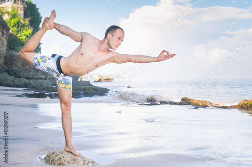 Handsome man doing yoga at cliff with blue sea background