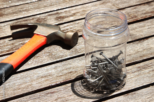 A hammer and a plastic jar of nails on a wooden table.  This image can be used to represent carpentry or DIY projects.